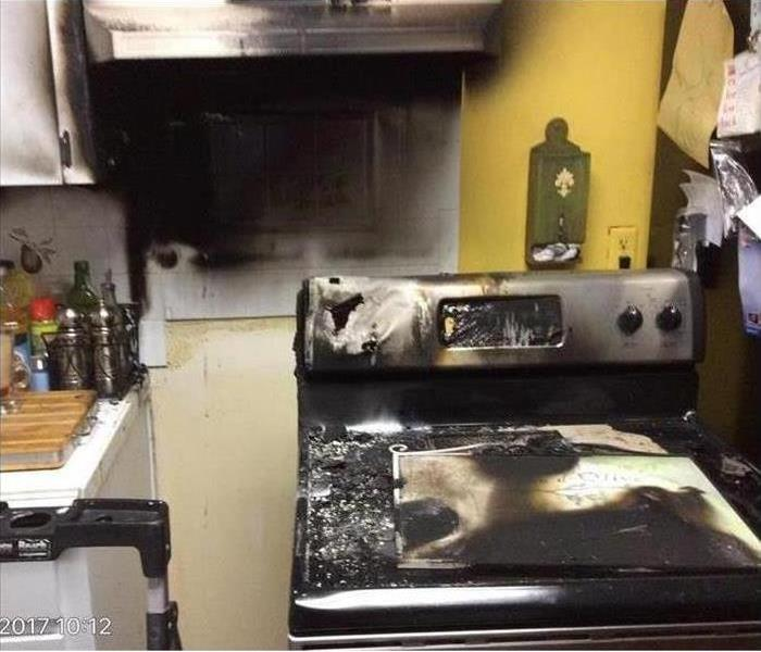 Kitchen stove & oven with burn marks and melted materials from a fire damage.